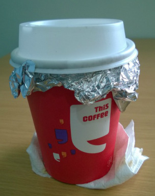 Coffee with foil between the lid and cup.